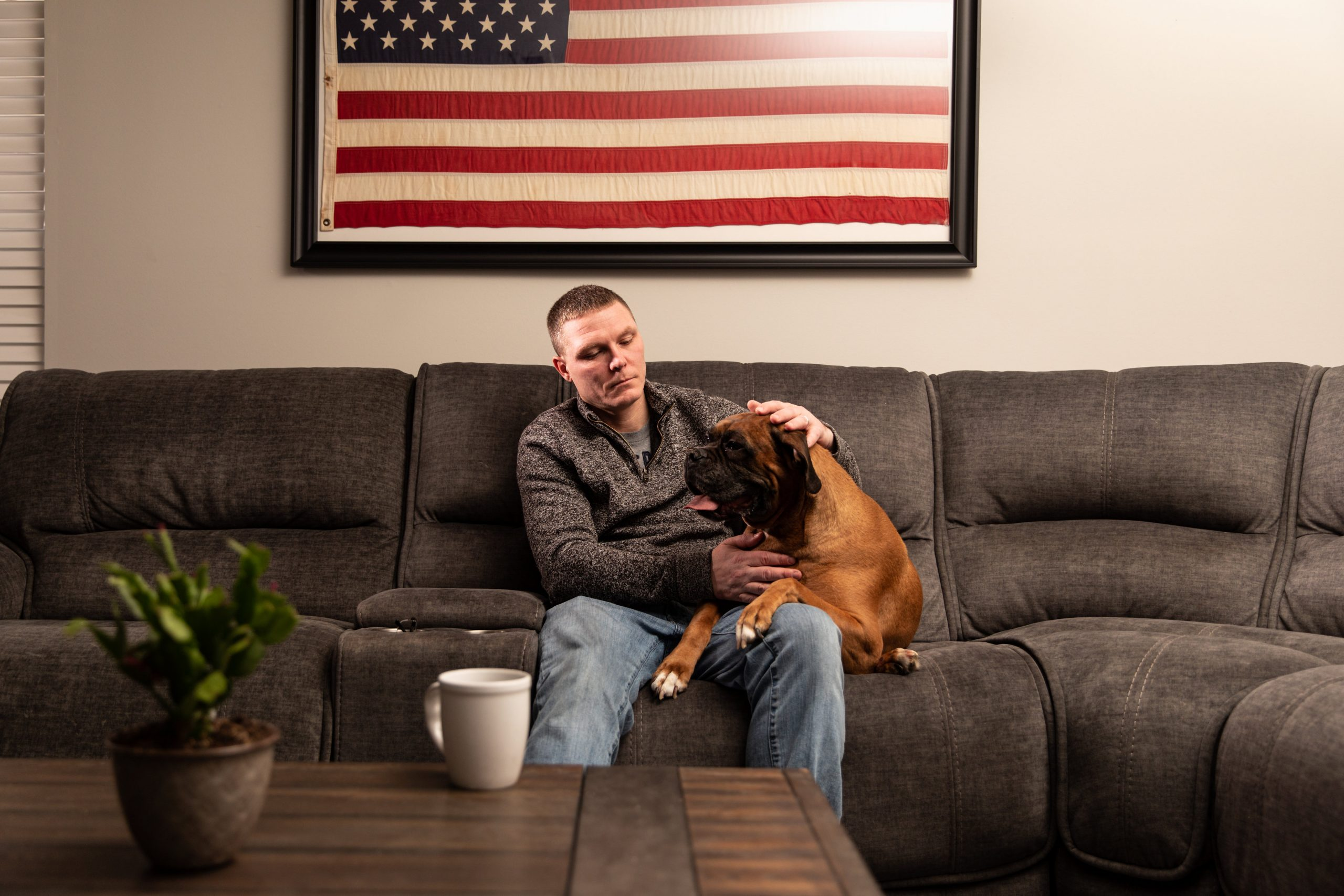 Veterans Companion Animal Services member lays on the couch with his dog