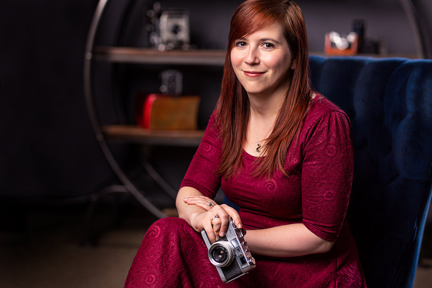 a woman poses with a vintage camera while wearing a dark red dress in front of a shelf of vintage cameras to demonstrate one of the tips for great branding photos