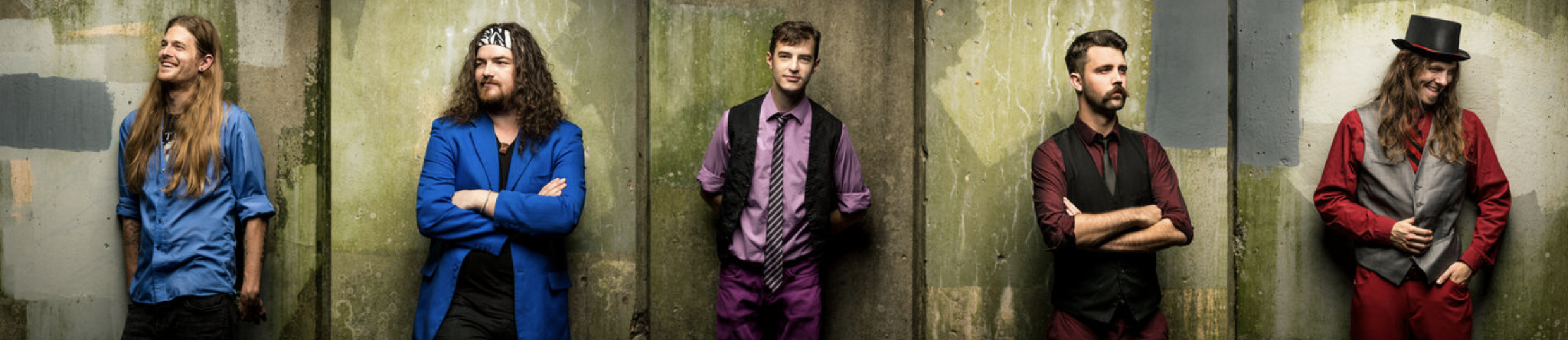 a group of male band members pose differently against a concrete wall while wearing different colored clothing to demonstrate one of the tips for great branding photos