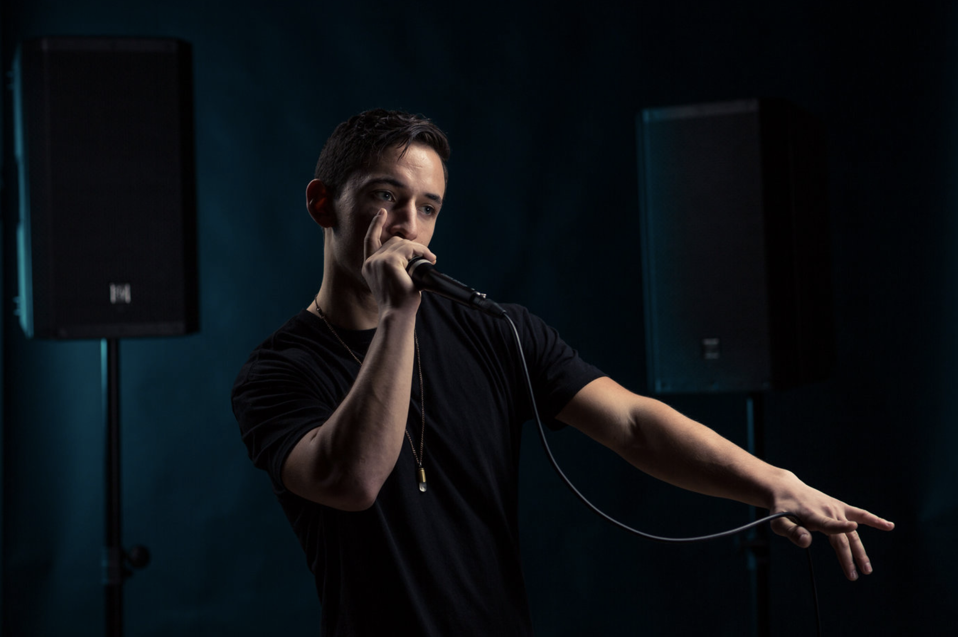 a beat boxer dances and beats with a microphone in his hand and speakers in the background