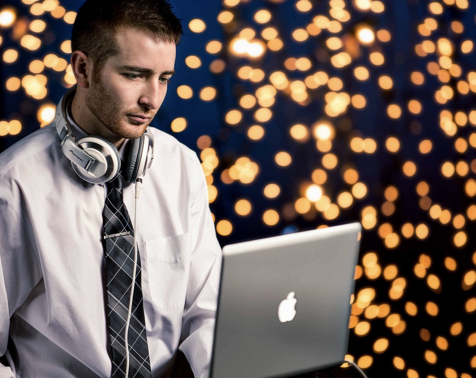 a DJ poses in front of a background full of string lights with a laptop and headphones to demonstrate one of the tips for great branding photos