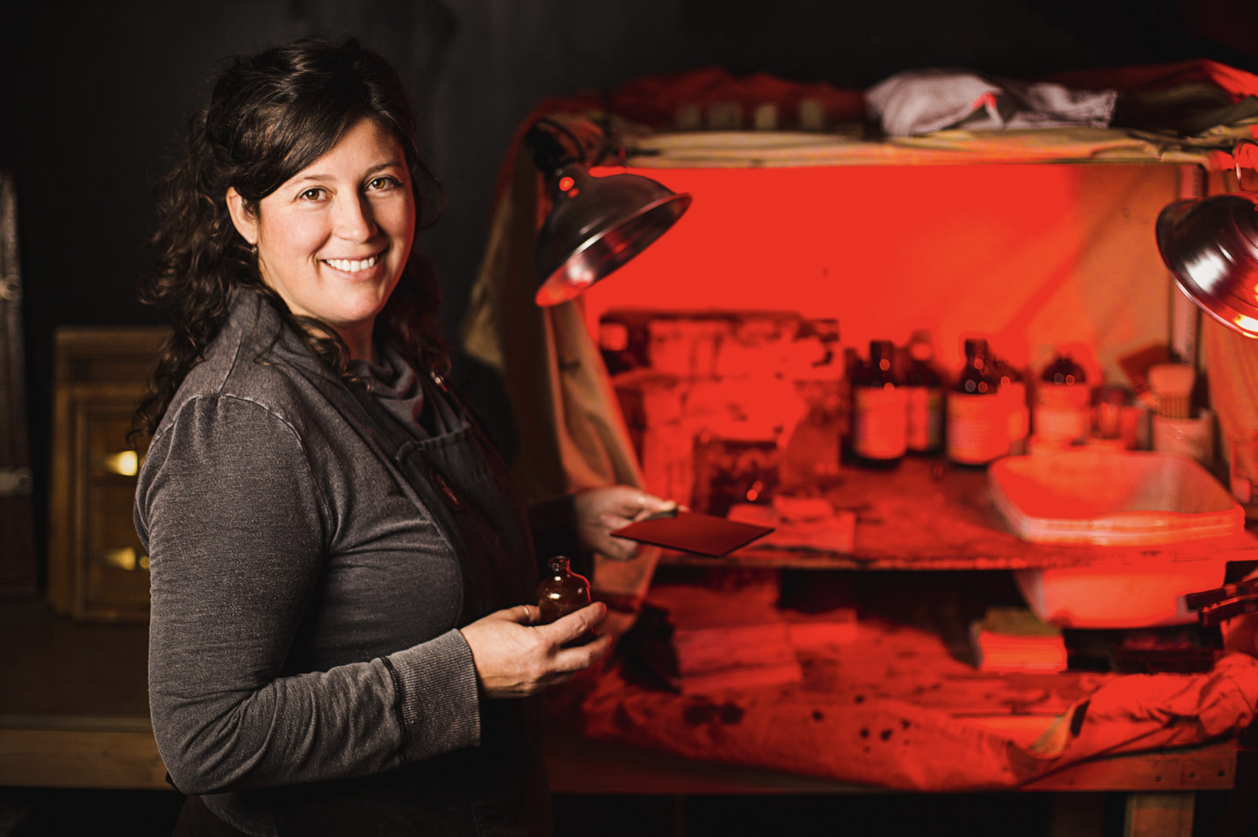 a female artist poses with her materials in front of a dark room set up to demonstrate one of the tips for great branding photos