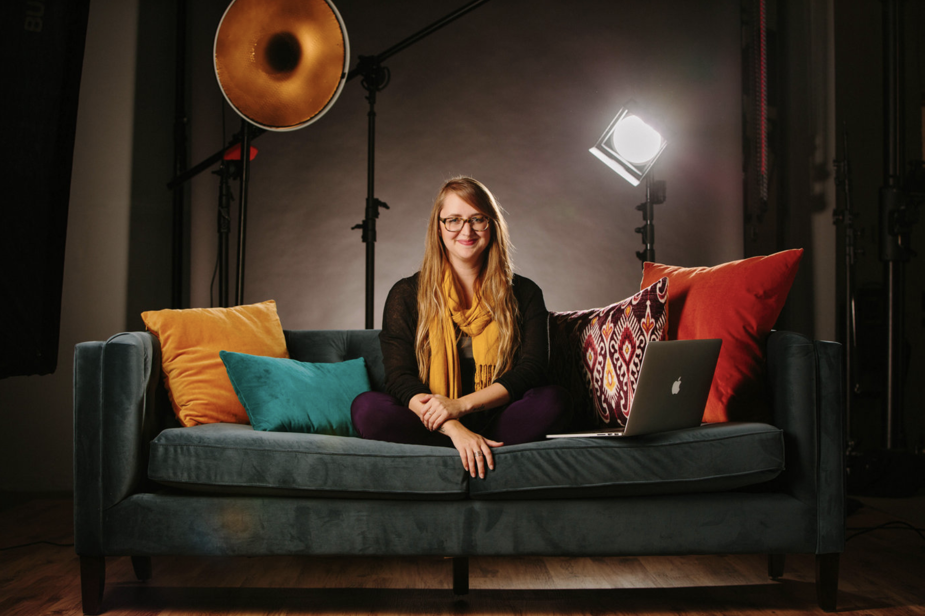 a blonde woman sits on a blue couch in a photo studio surrounded by colorful pillows to demonstrate one of the tips for great branding photos